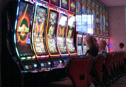 This June 20, 2019 photo shows gamblers playing slot machines at the Hard Rock casino in Atlantic City N.J. As of March 16, 2020, casinos in at least 15 states had shut down due to the coronavirus, including Atlantic City's nine casinos which were due to close at 8 p.m. (AP Photo/Wayne Parry)